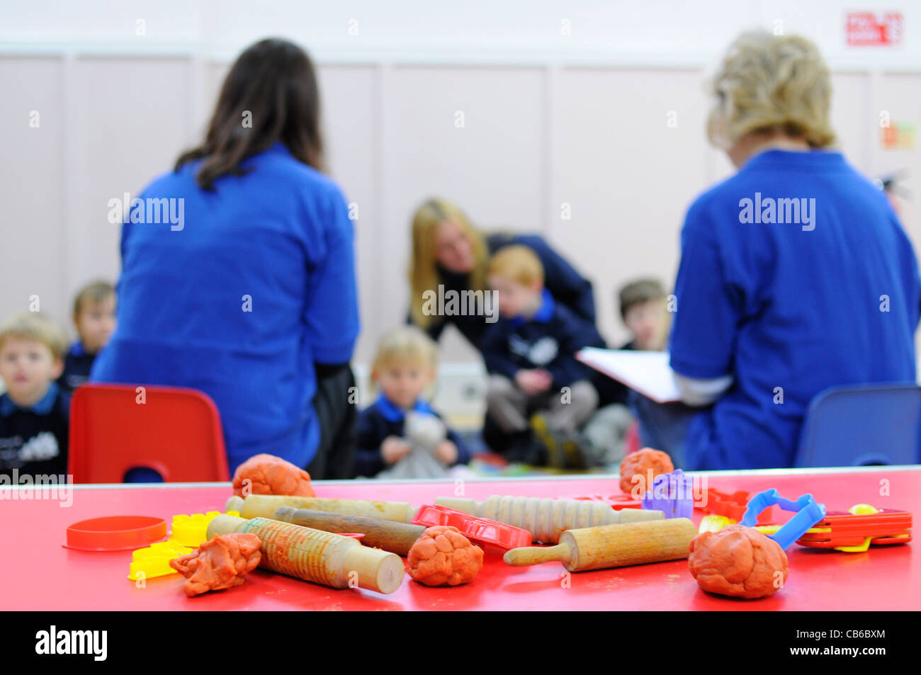 Preschool group UK Children and teachers with activity in foreground. - Stock Image