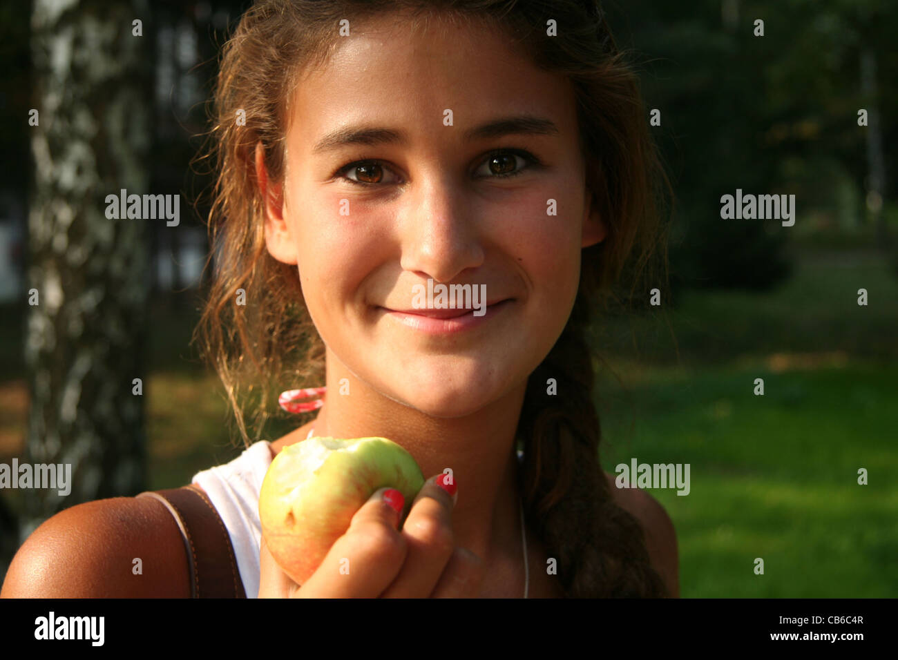 Portrait of a young teenager, girl, ready to eat an apple. Outside, garden, natural lighting, straight look, summer. - Stock Image