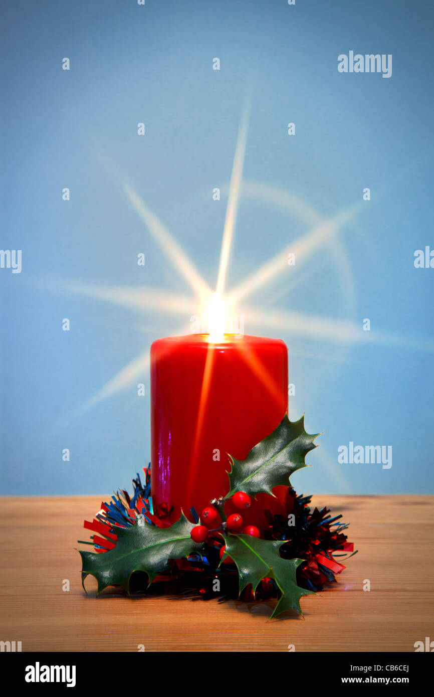 Photo of a Christmas candle and holly with starburst, the star from the flame was created in camera using a filter. - Stock Image