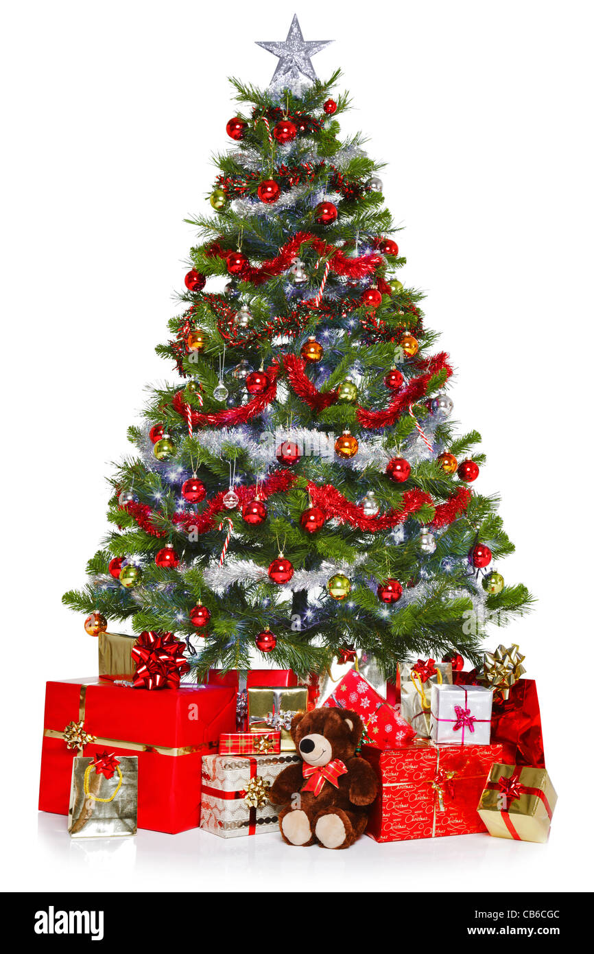 Photo of a Christmas tree with decorations and lights surrounded by presents, isolated on a white background. - Stock Image