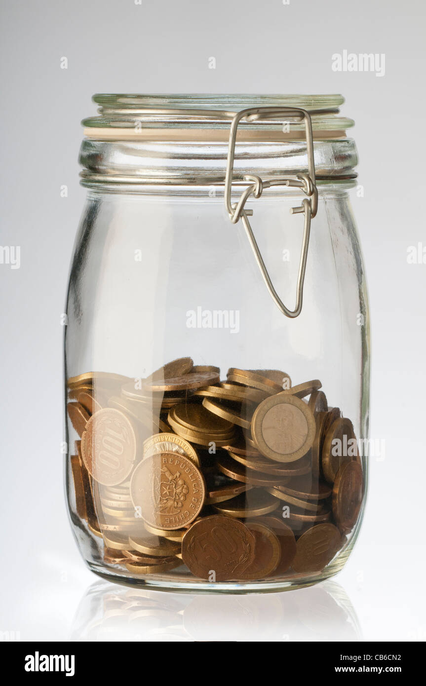 different coins values ​​in a glass jar - Stock Image