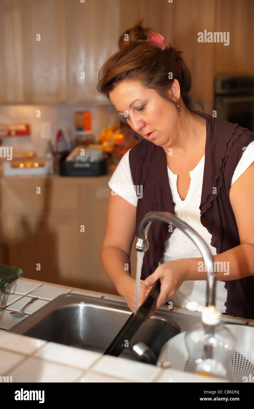 Dishwashing - Woman cleaning dishes after cooking in her ...