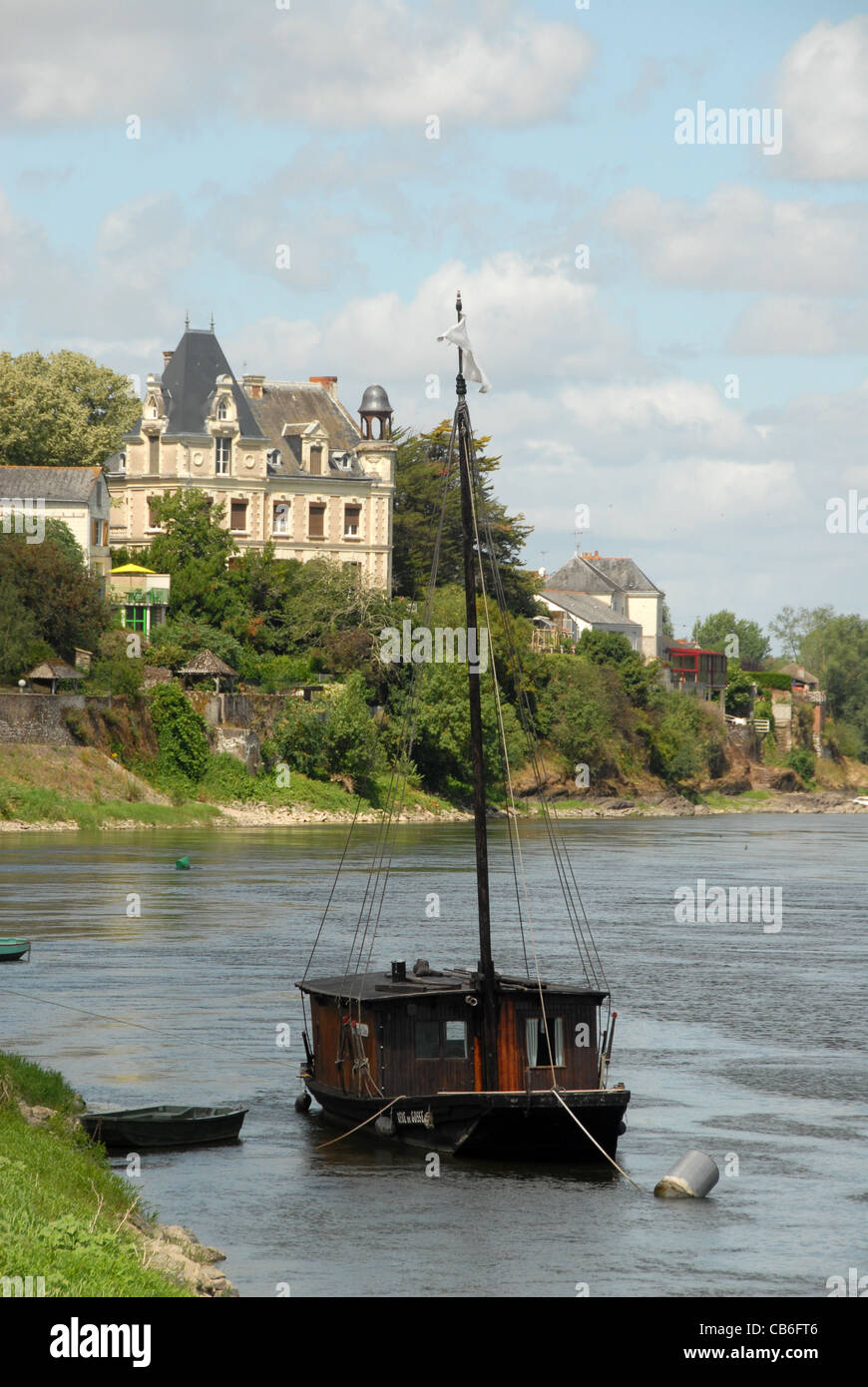 Traditional vessel and hôtel particulier on the banks of the Loire river at Quai Gambetta, Chalonnes-sur-Loire - Stock Image