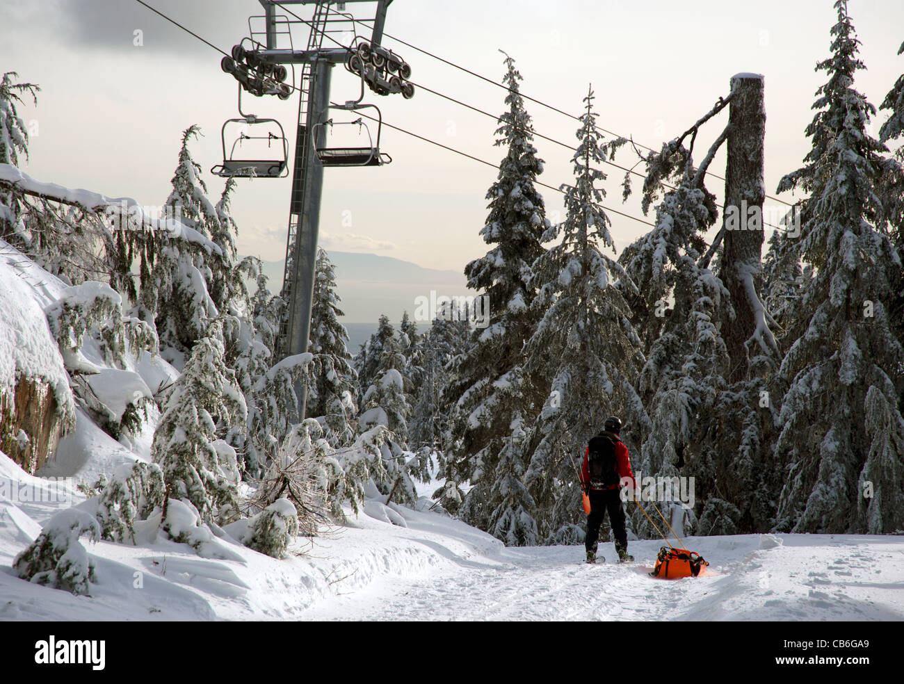 Rescue sled being towed near chairlifts at Grouse Mountain Ski Resort, Vancouver, British Columbia, Canada Stock Photo