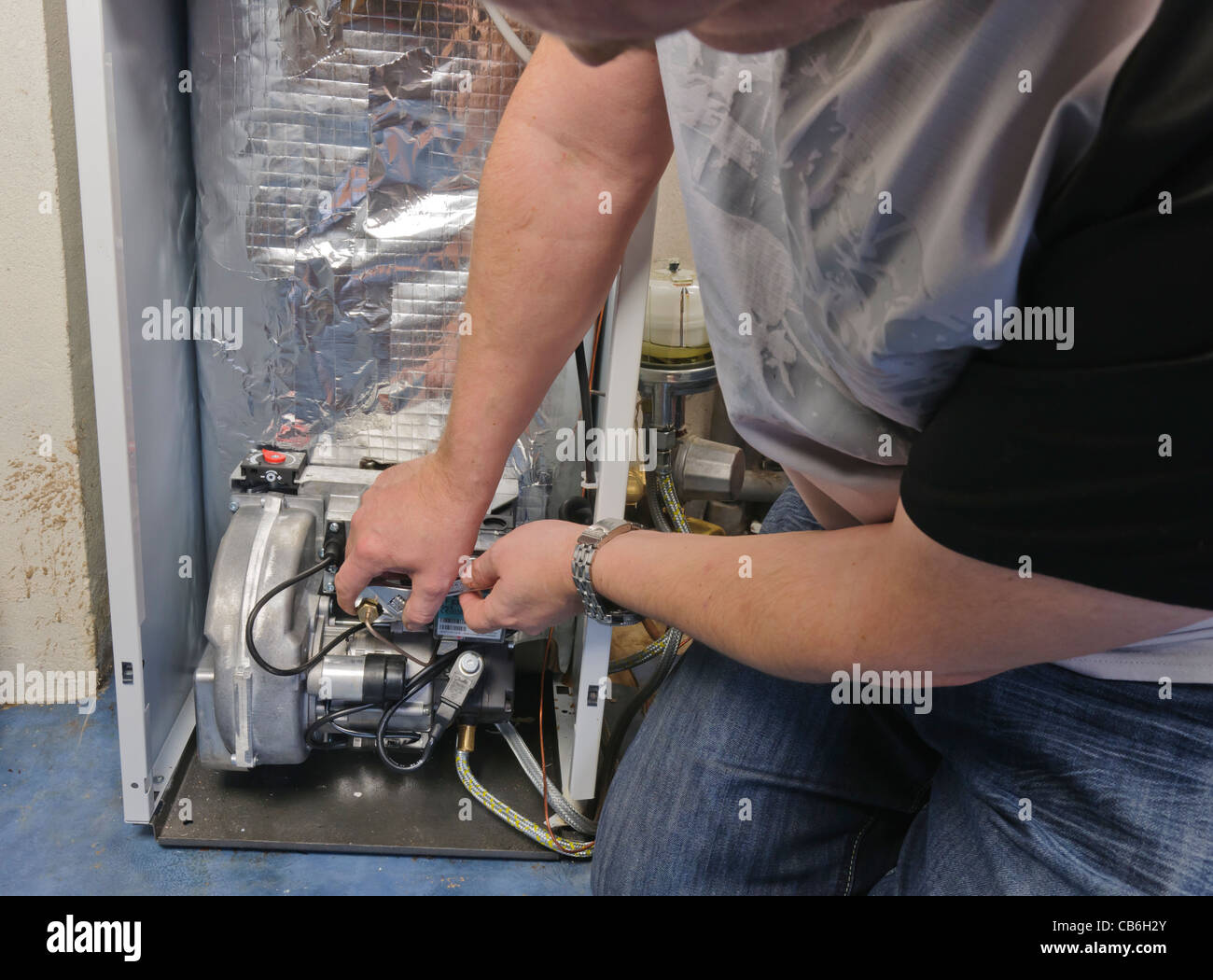 Man servicing the burner on an oil-fired domestic central heating boiler. - Stock Image