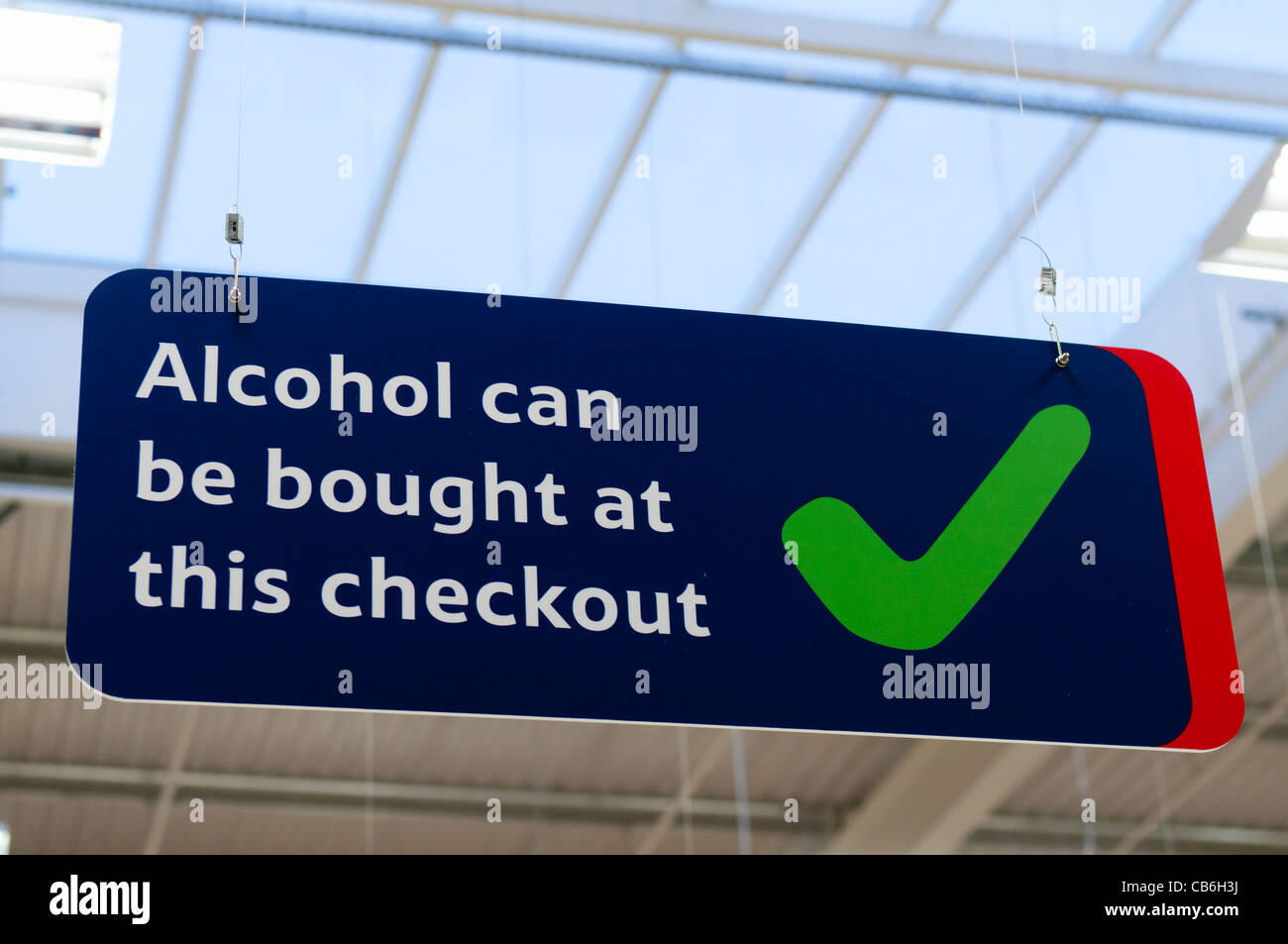 Sign advising customers that alcohol can be purchased at this checkout (Northern Ireland Licencing laws) - Stock Image
