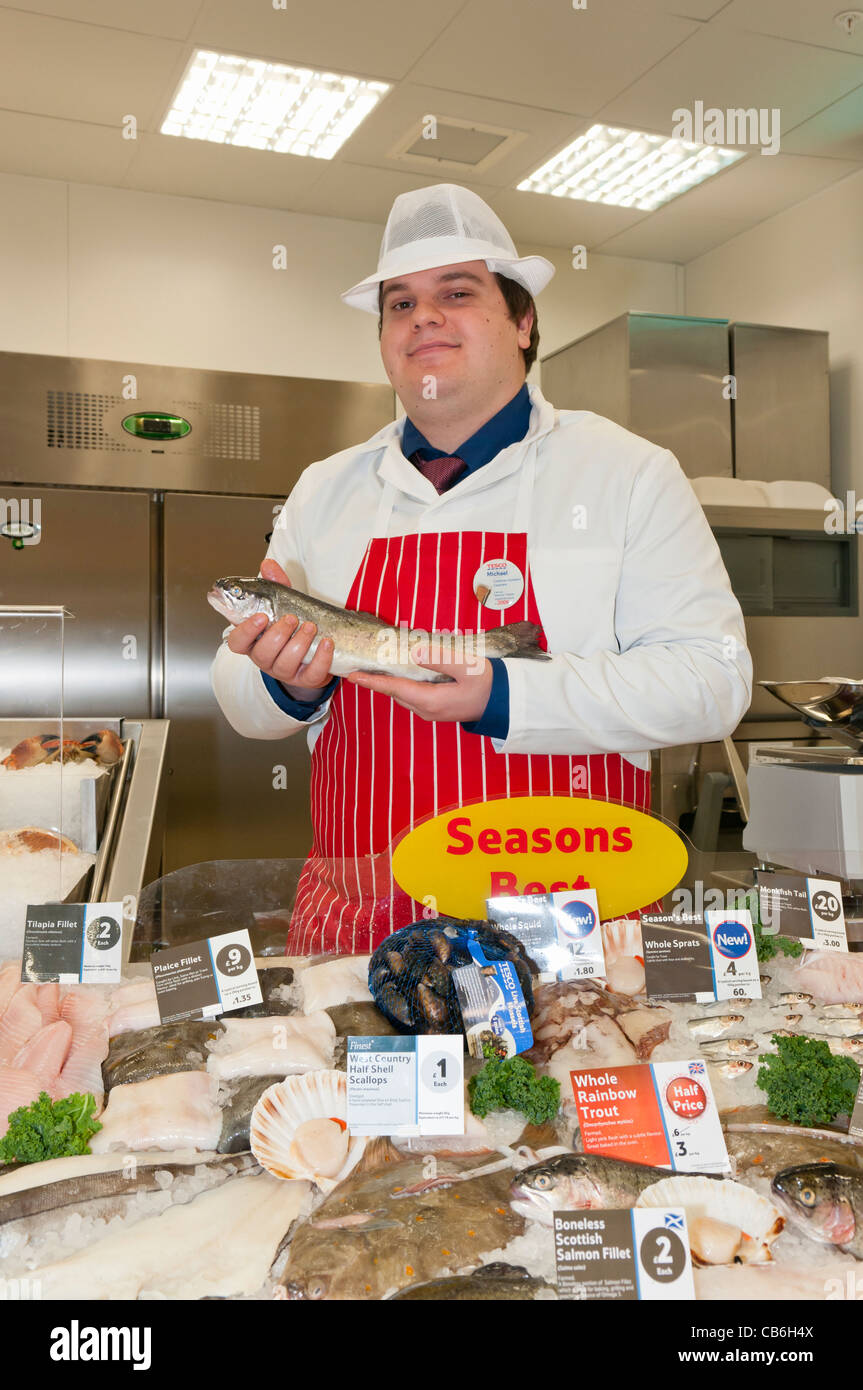 Man holds a rainbow trout at the fish counter in a Tesco Store - Stock Image
