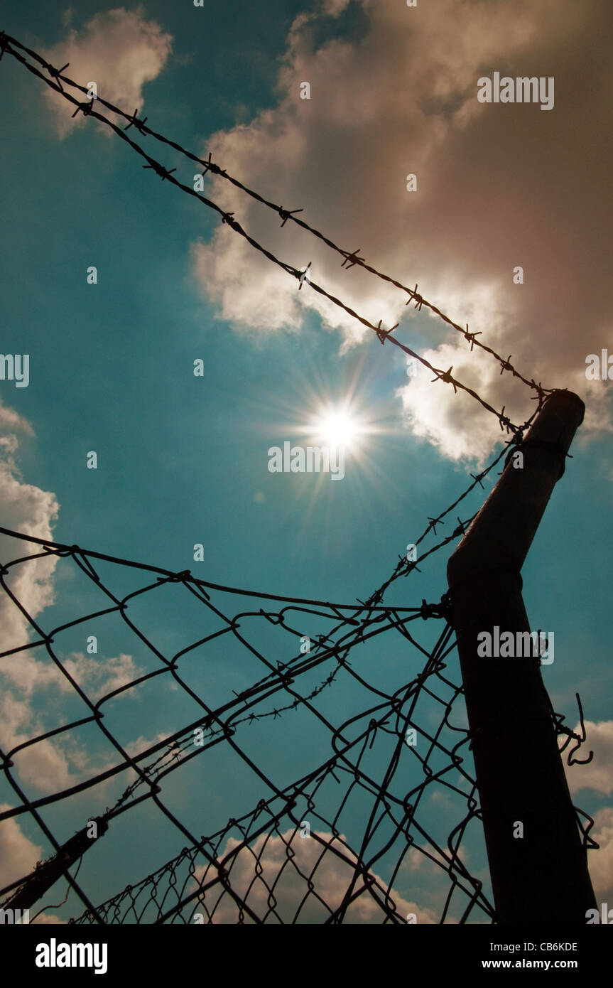Barbed wire fence against a blue sky with clouds - Stock Image