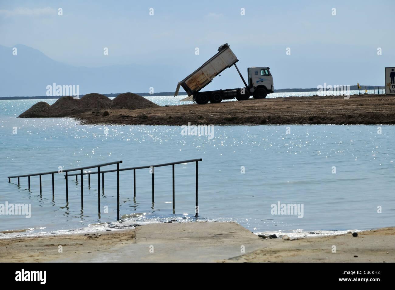 Dumping truck dumping soil for new beach,Dead Sea, Israel, Asia - Stock Image