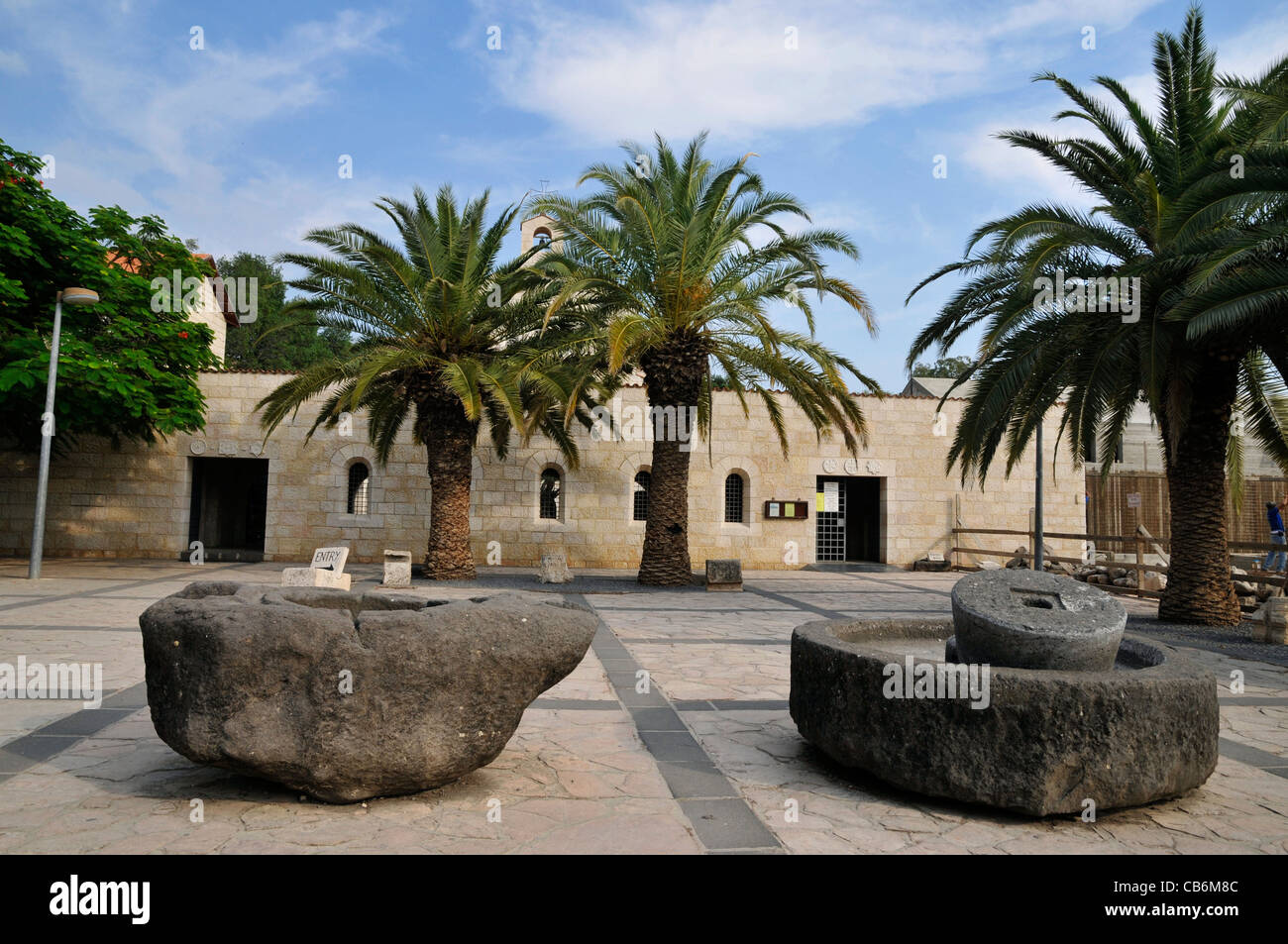 Tabgha Church Of The Multiplication with Olive Oil Press in front, Galilee, Israel - Stock Image