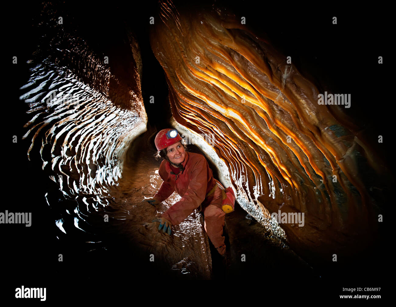 Female caver with stalactite curtain in French cave Stock Photo