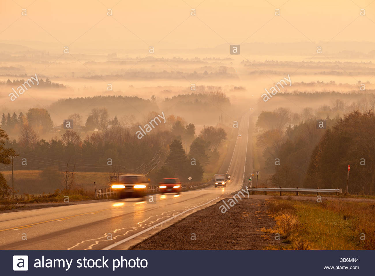 Commuters and rolling farmland early on a autumn morning in a radiation type fog in Durham region in Ontario Canada - Stock Image