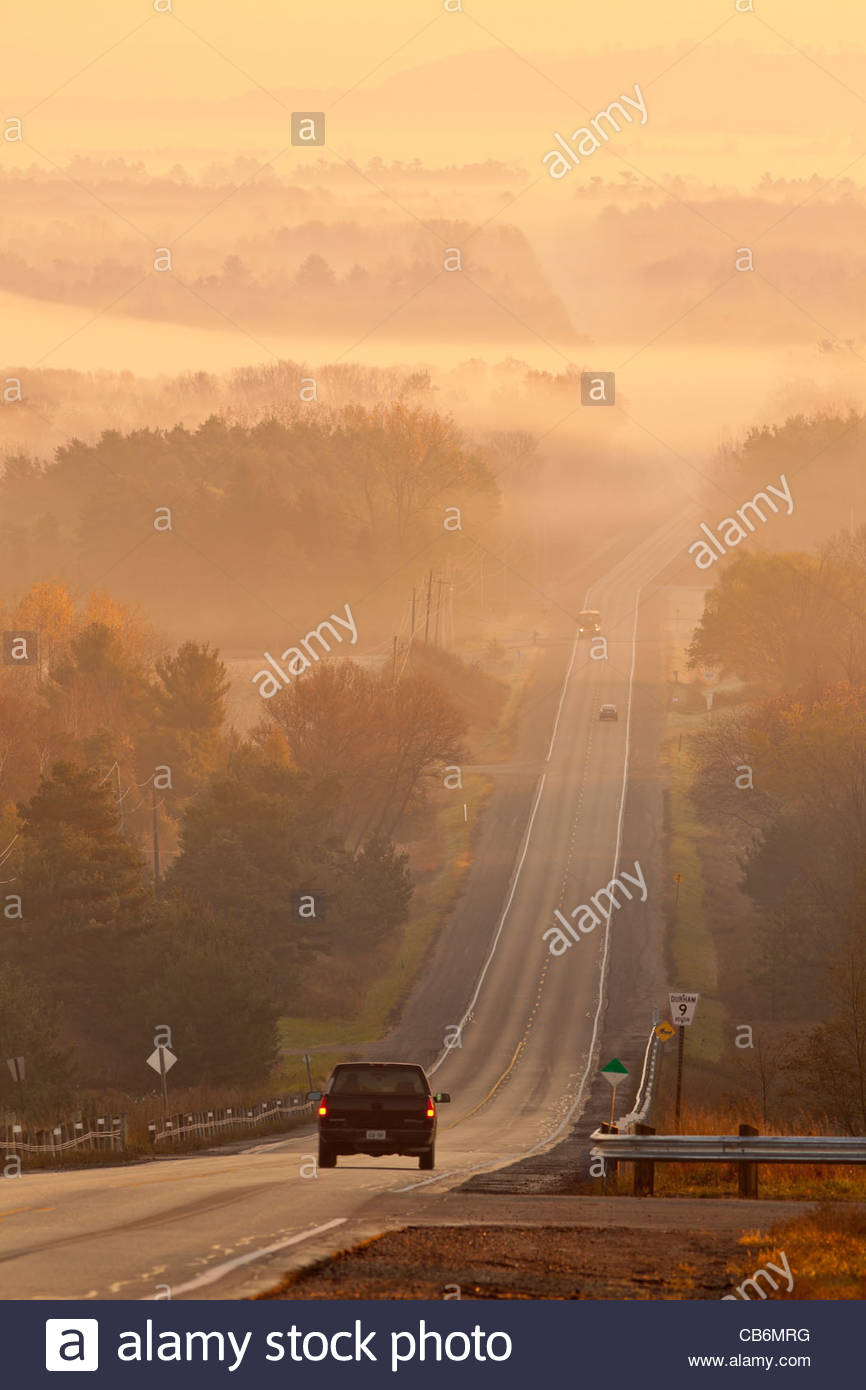 Road and rolling farmland early on a autumn morning in a radiation type fog in Durham region in Ontario Canada - Stock Image