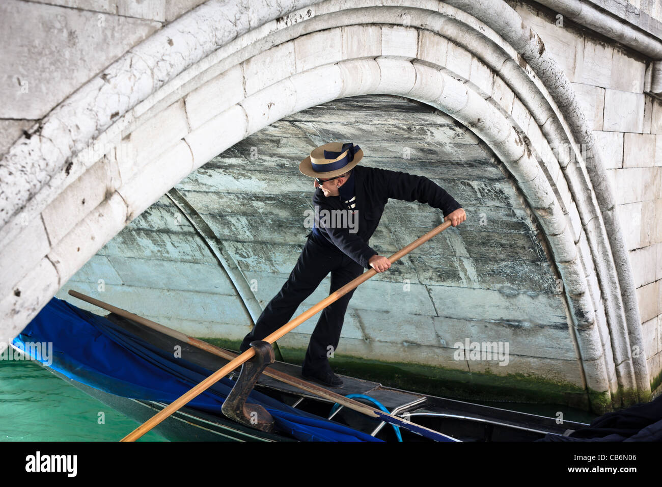 Gondolier and his gondola moving under a small bridge in Venice, Italy - Stock Image