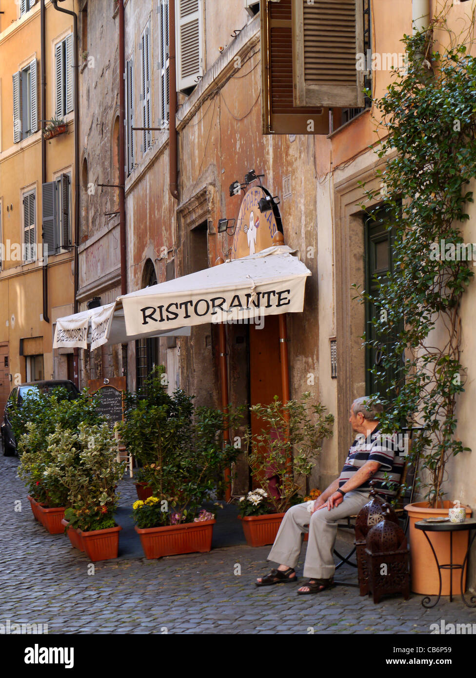 Medieval street in Rome with restaurant awning - Stock Image