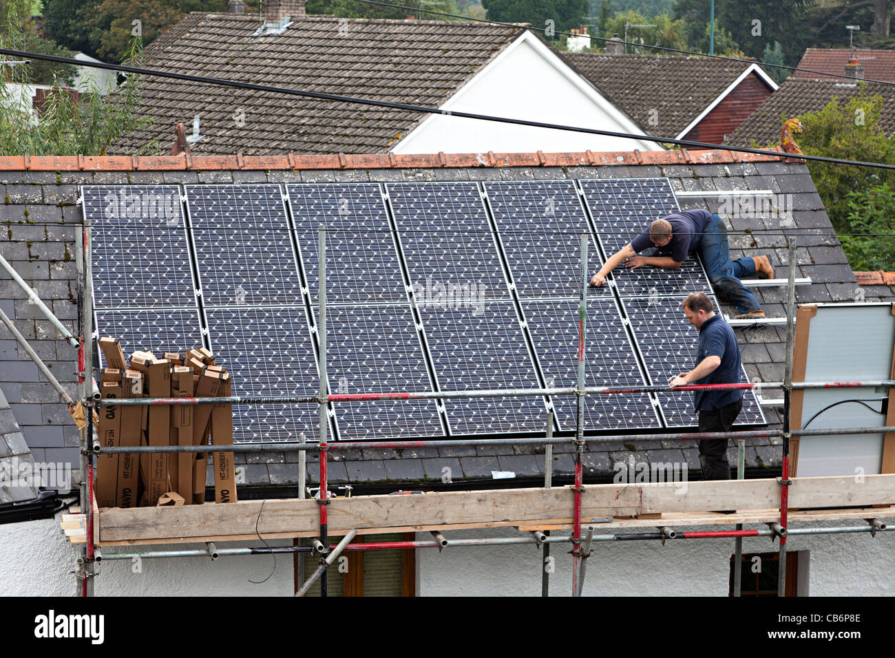 Two men fitting solar panels to house rooftop in village Wales UK - Stock Image