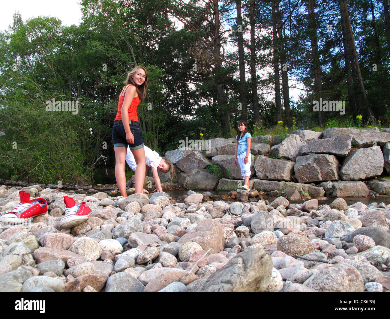 Two young girls playing on stony river bed Stock Photo