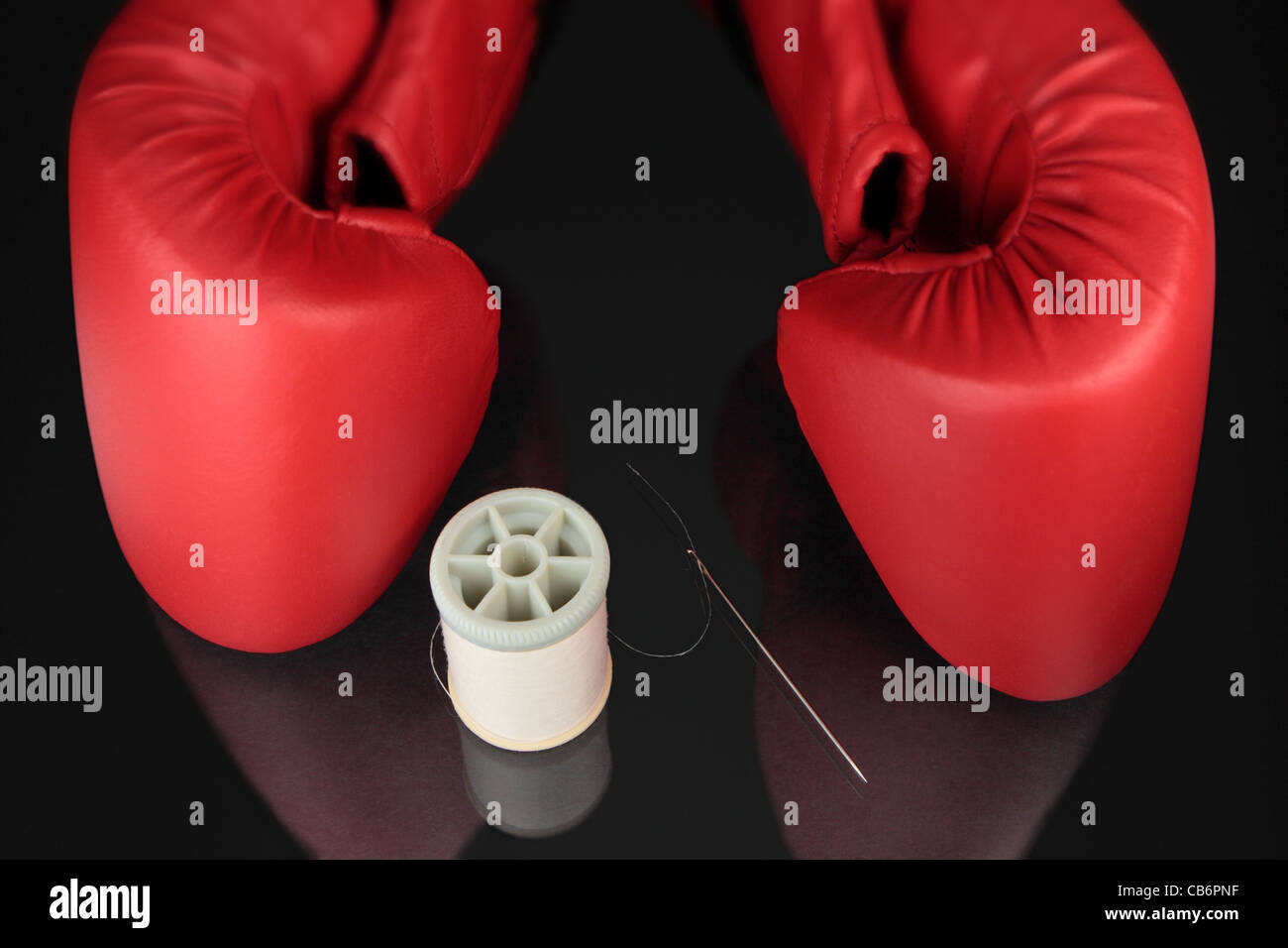 a spool of thread, sewing needle and boxing gloves on black reflective surface - Stock Image