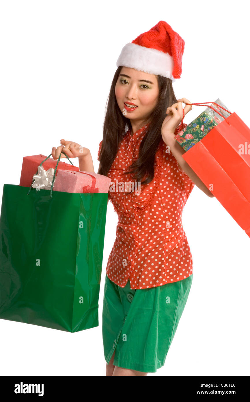 fd71fe7da55df Asian female in Santa hat with bags full of gifts Stock Photo ...