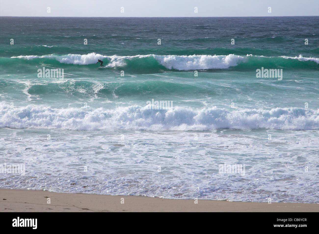 Surfer in rough seas off Porthmeor beach, St Ives, Cornwall, Southwest England, UK, United Kingdom, GB, Great Britain - Stock Image