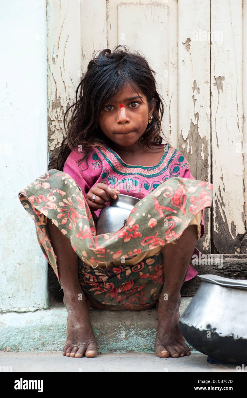 Poor Indian nomadic beggar girl sitting on an indian street begging. Andhra Pradesh, India - Stock Image