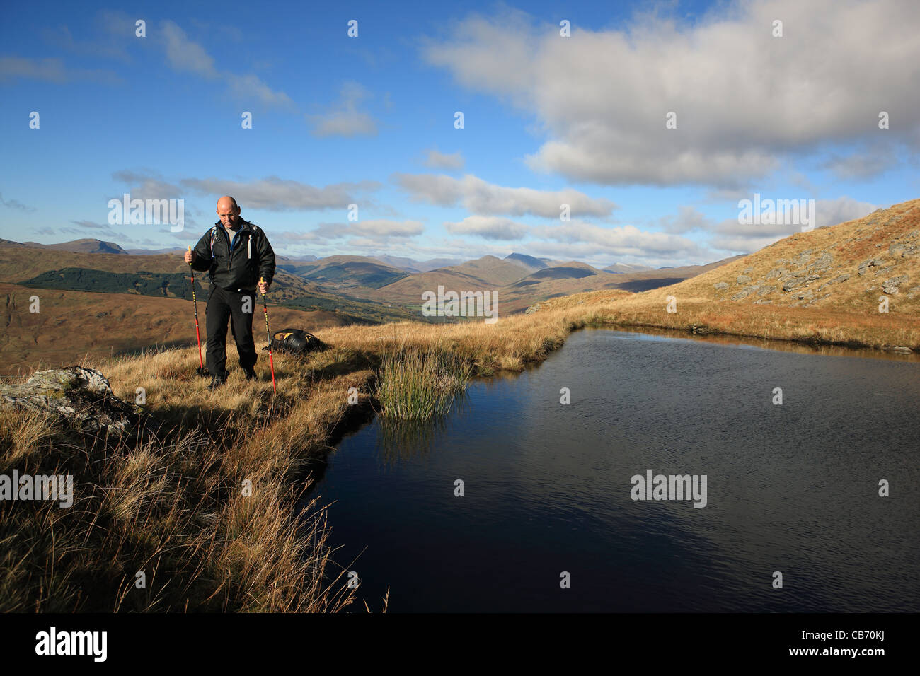 Hillwalker walking around a Lochan on the slopes of Cruach Ardrain with the mountains beyond Tyndrum in the background - Stock Image
