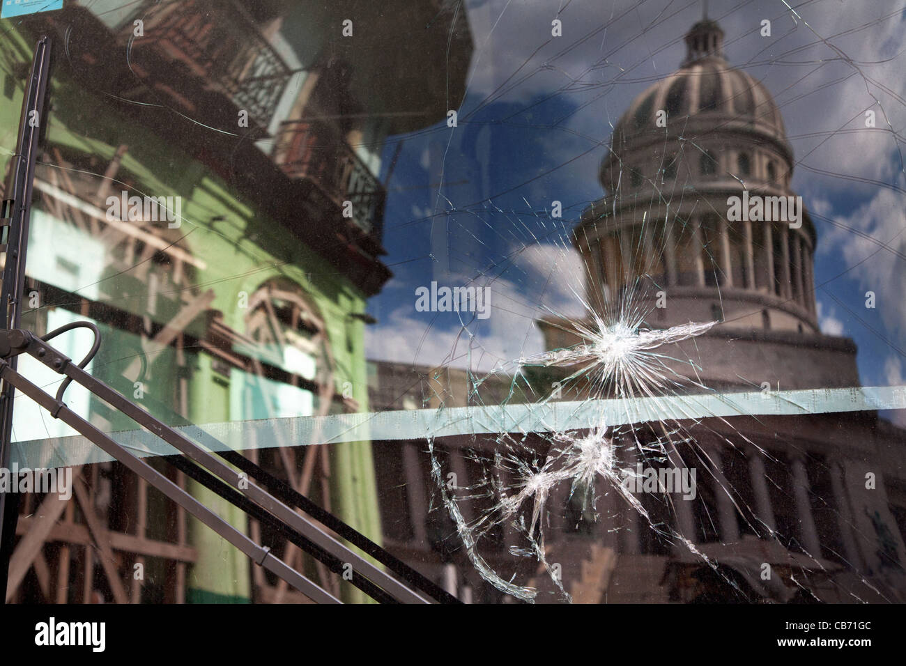 The Capitolio and the buildings of Paseo Marti reflect in a cracked bus window, Havana (La Habana), Cuba - Stock Image