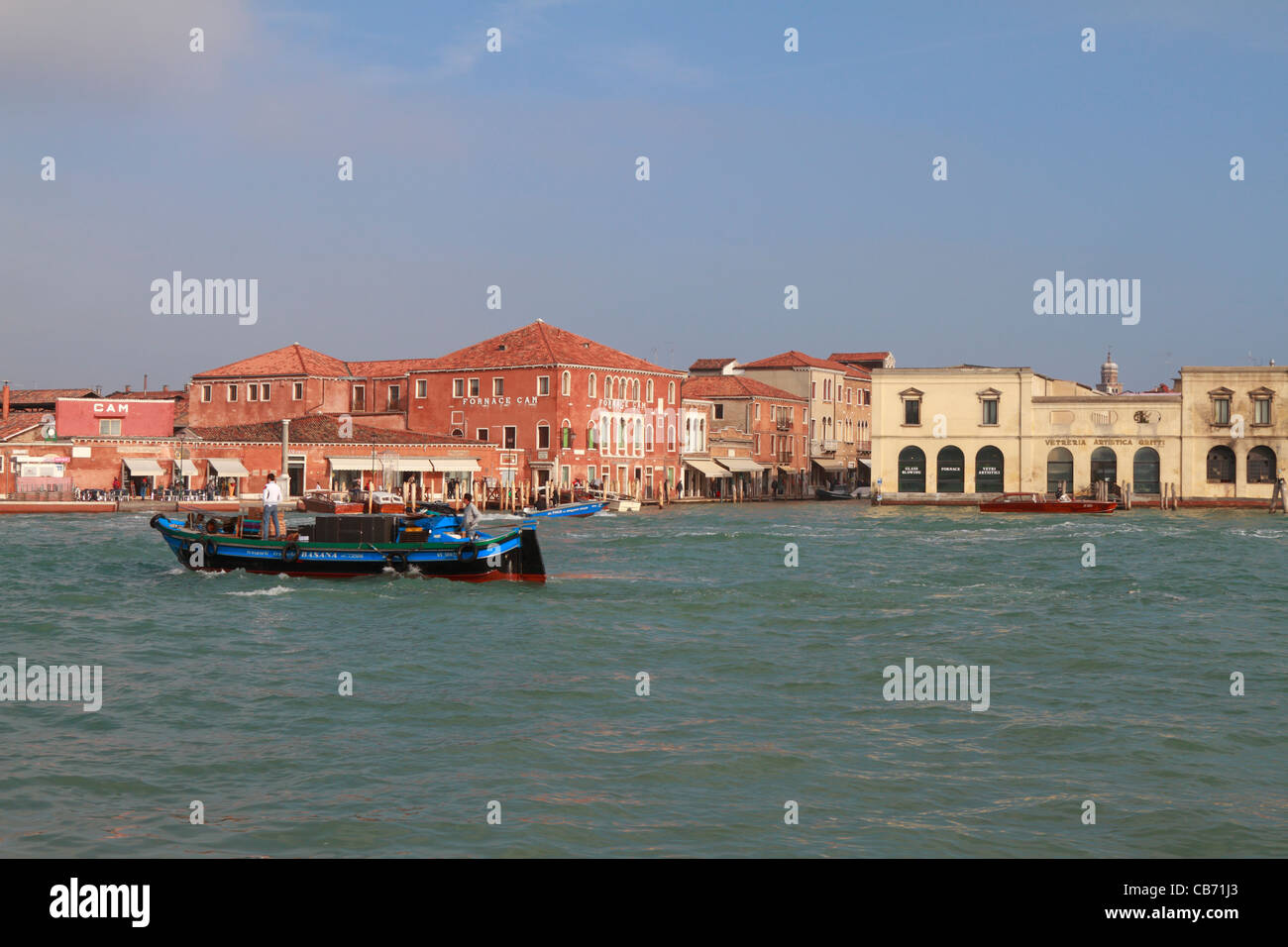 A fishing boat passes fornace glass factories, Murano, Italy, Europe. - Stock Image