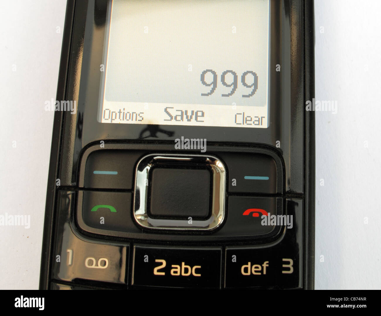 A simple Nokia mobile phone on a white background closeup of the screen showing 999 UK emergency services number - Stock Image