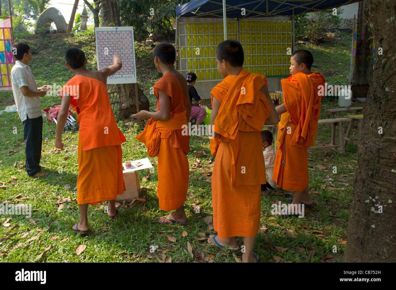 Novice Buddhist monks throwing darts at a sideshow, Lao New Year (Pi Mai Lao), Luang Prabang, Laos - Stock Image