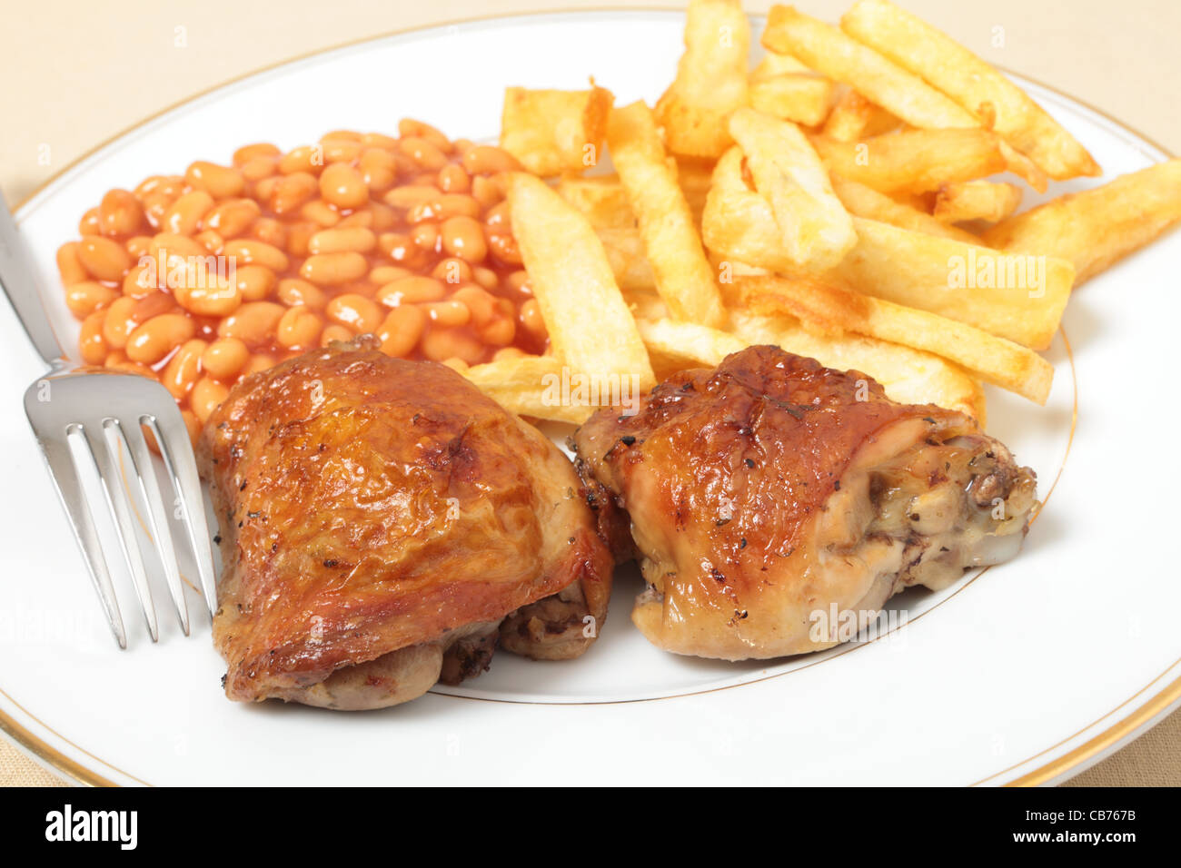 A meal of lemon chicken with french fries and baked beans - Stock Image