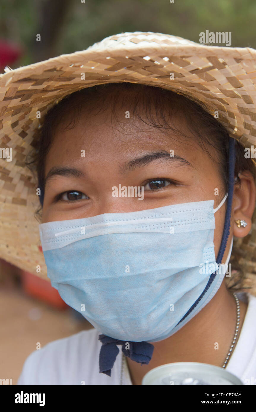 Khmer woman in a surgical mask at a village festival, Cambodian New Year (Chaul Chnam Thmey), Bakong Village, Siem Stock Photo