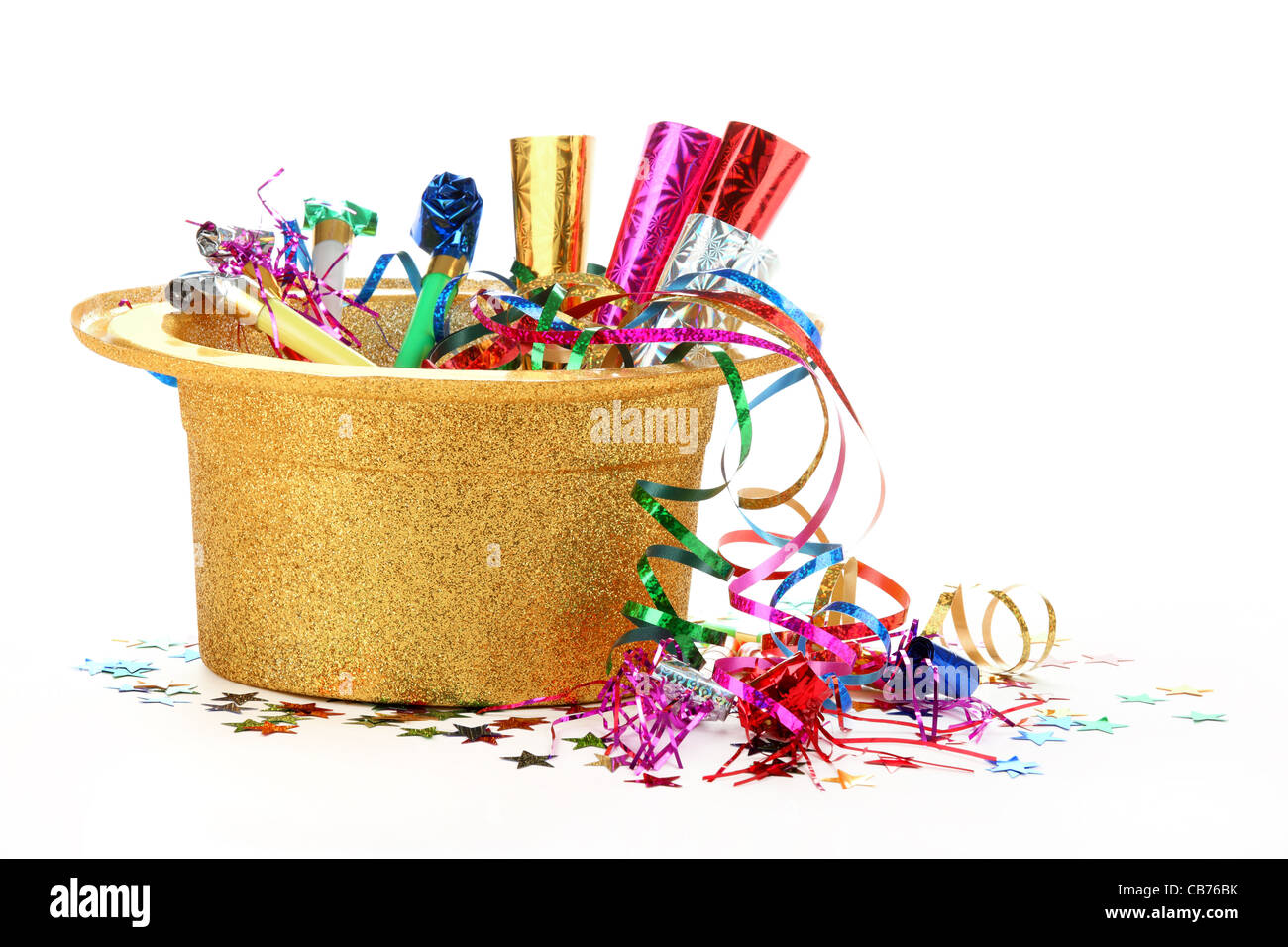 New Year's hat filled with noise makers, streamers and confetti on white background. - Stock Image