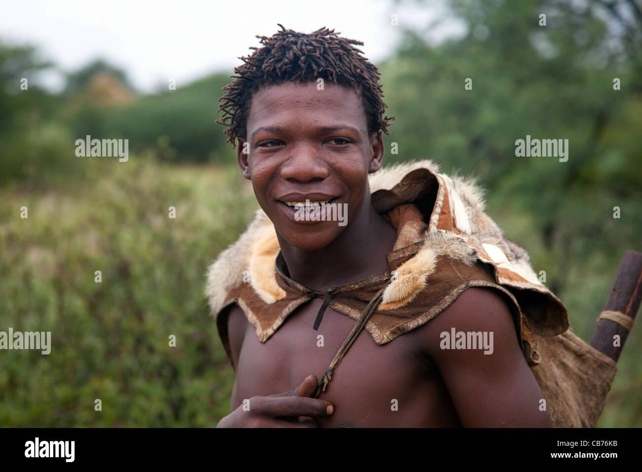 Bushman dressed in animal skin in the Kalahari desert near Ghanzi, Botswana, Africa - Stock Image