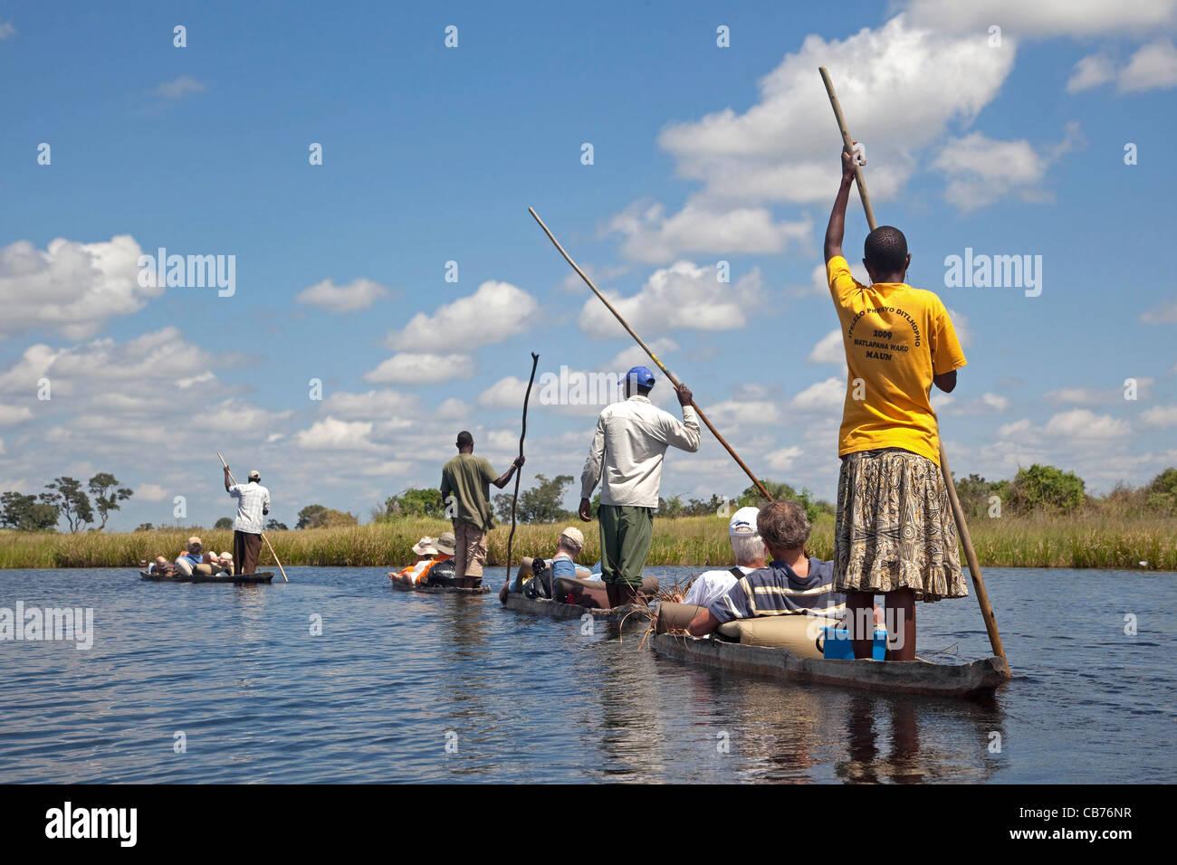 Tourists traveling in traditional wooden canoes, mokoro / makoro in the Okavango Delta, Botswana, Africa - Stock Image