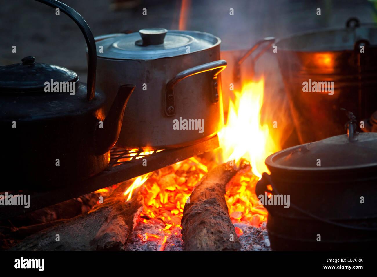 Boiling water in kettle and food cooking in metal pots on open wood fire, Okavango Delta, Botswana, Africa - Stock Image
