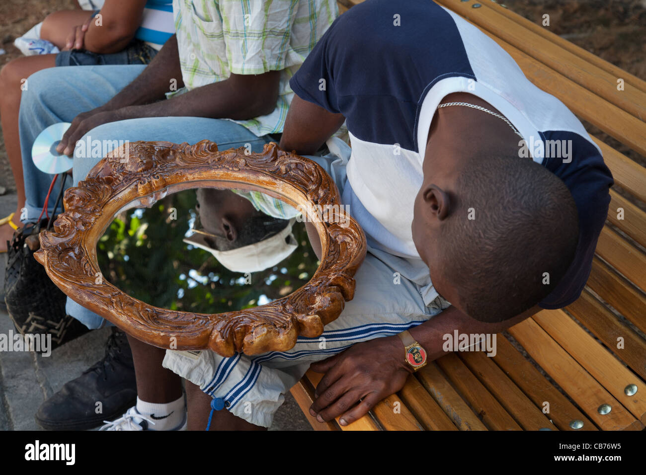 A young man checks his recent acquisition, a mirror, Havana (La Habana), Cuba - Stock Image