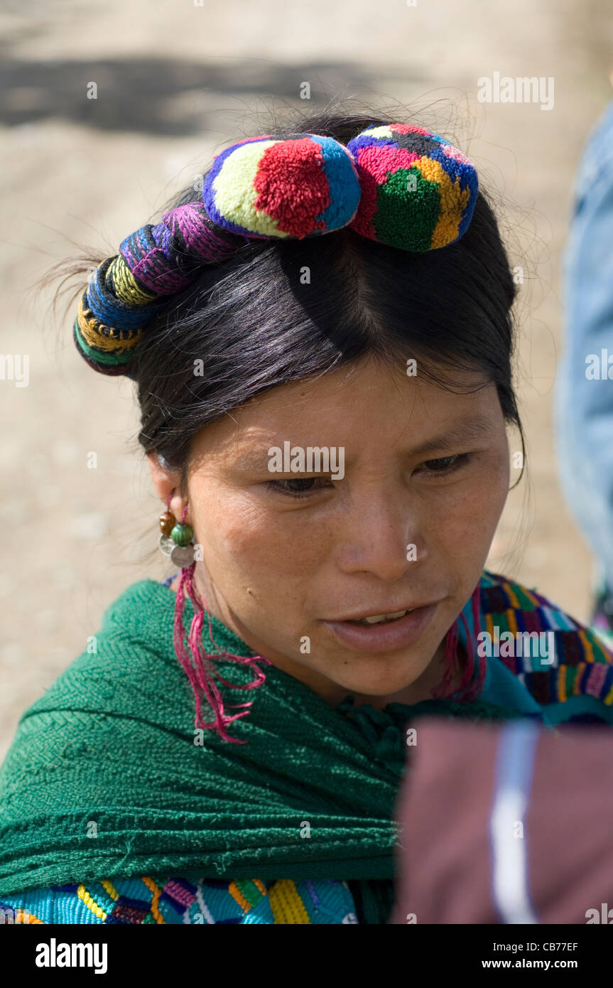 indigenous Central American Indian woman in traditional woven clothing and with colored braids and pom-poms in her - Stock Image