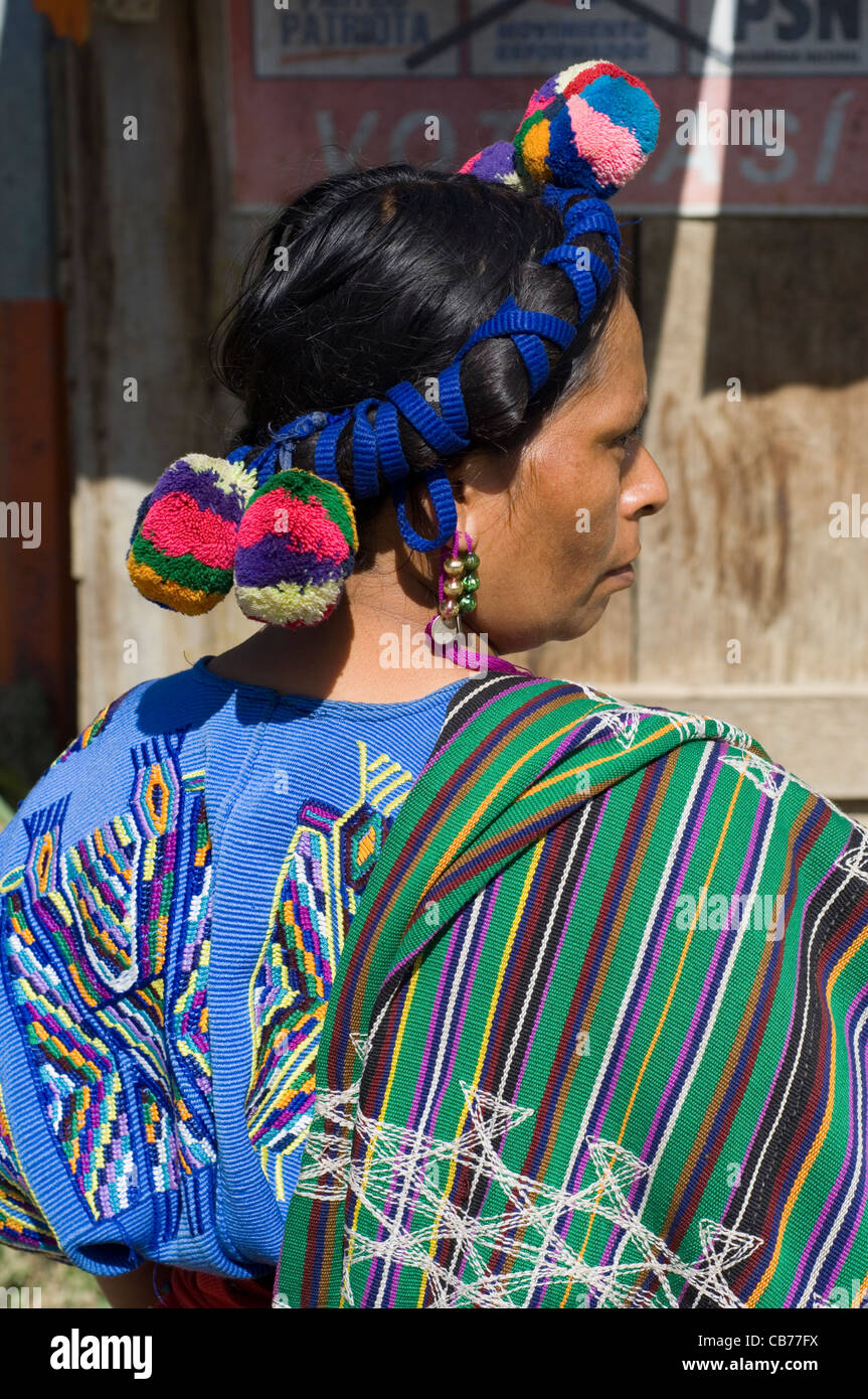 An indigenous Central American Indian woman in traditional woven clothing and with colored braids and pom-poms in - Stock Image