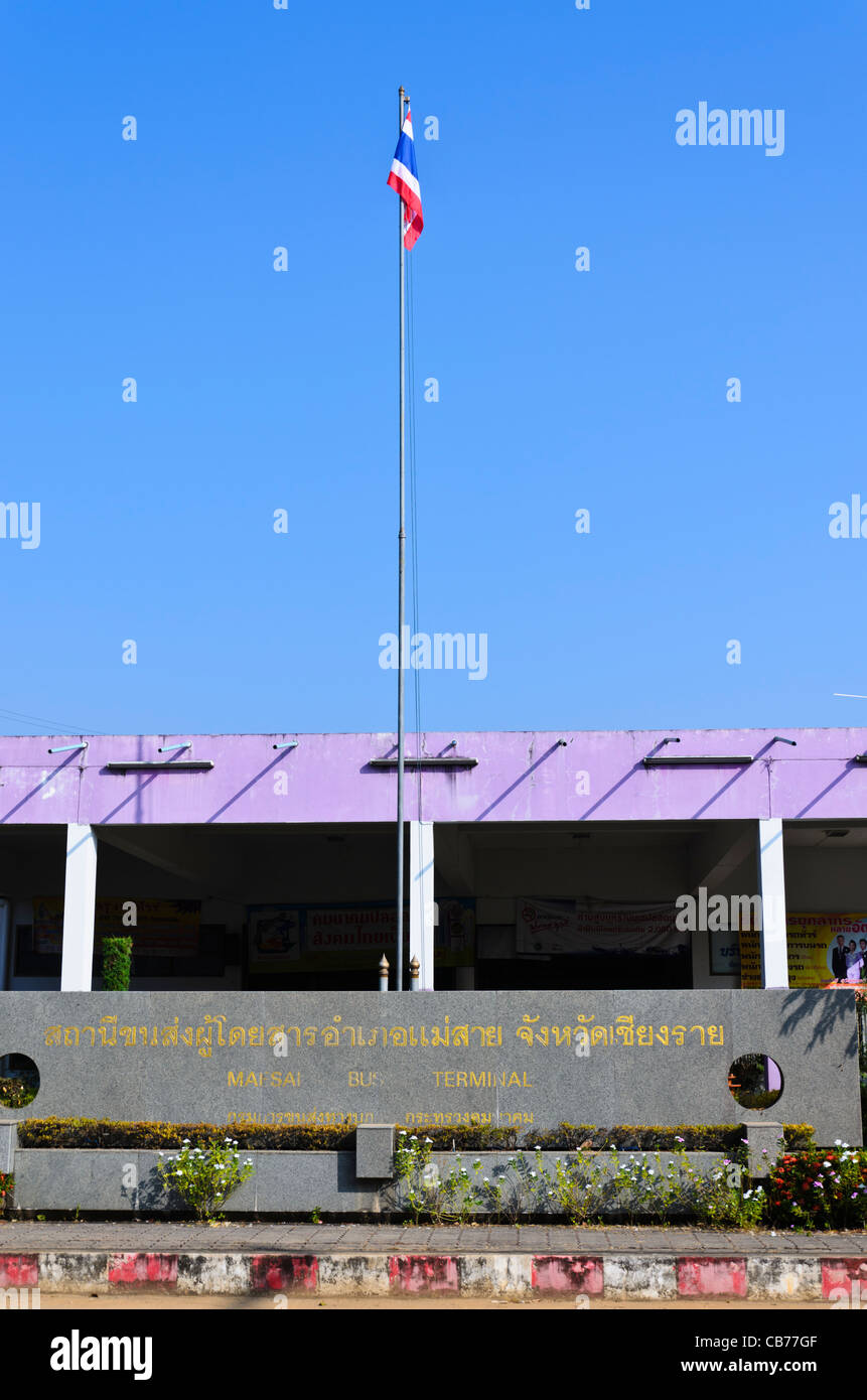 Large sign saying 'Maesai Bus Terminal' & a tall flagpole in front of bus station on a sunny clear day - Stock Image