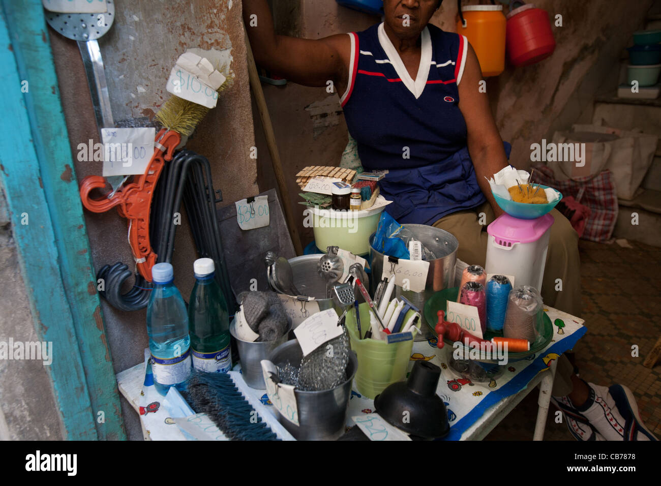A woman selling stuff and staples in the street at the front of her home, Havana (La Habana), Cuba - Stock Image