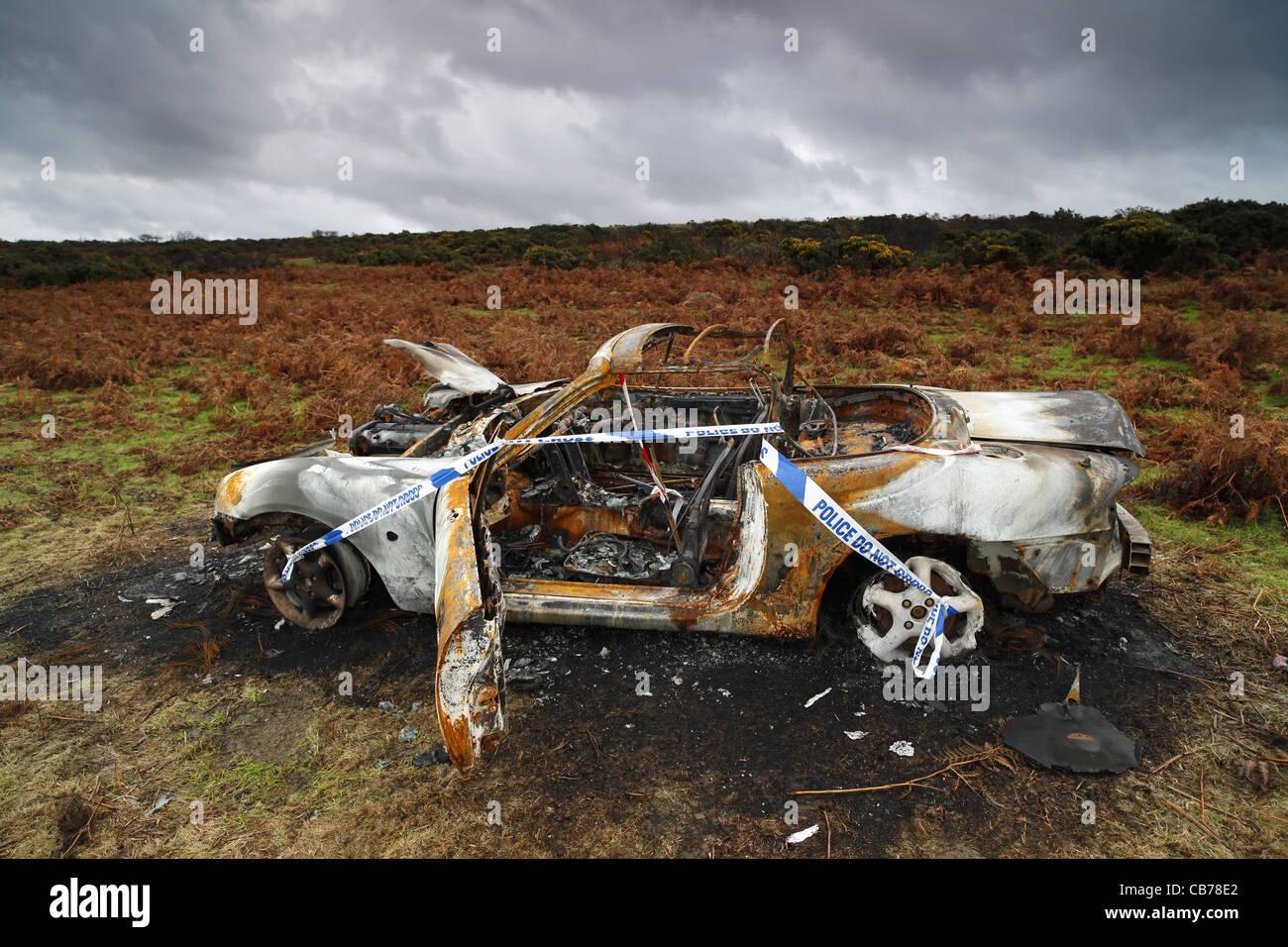 A burnt out Mazda MX5 on Dartmoor in Devon, UK. - Stock Image