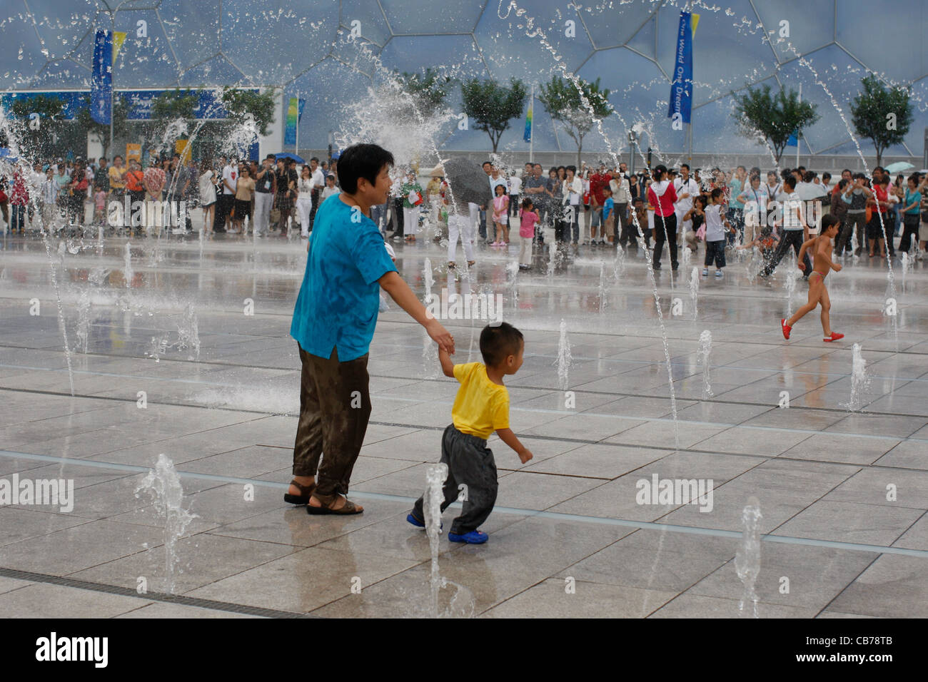Beijing, China: Chinese couples, families and kids enjoy the vast plazas outside the National Stadium during Paralympics - Stock Image