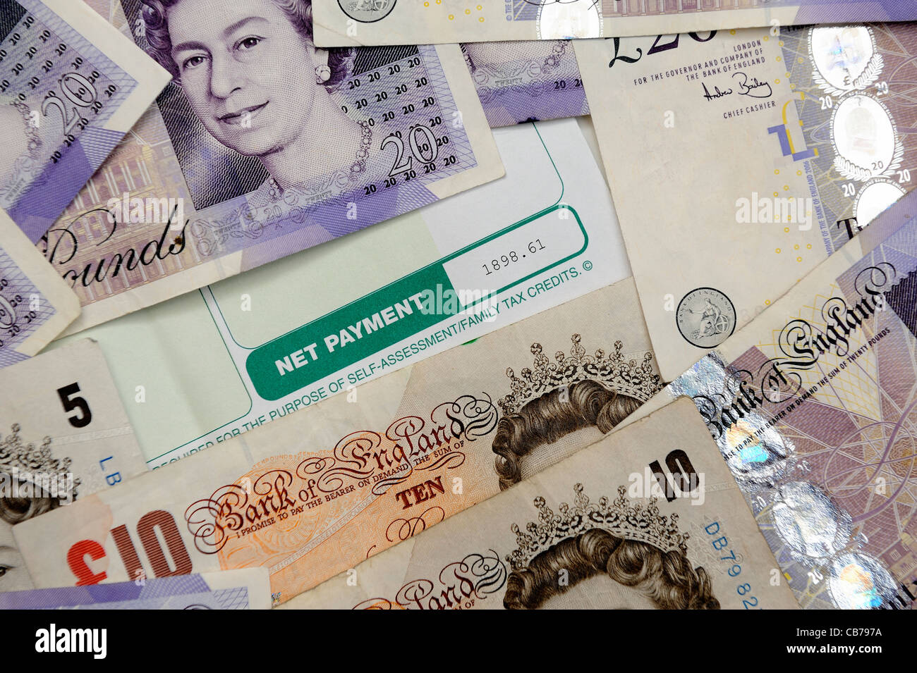 net payment on payslip surrounded by english 10 and 20 pound notes uk - Stock Image