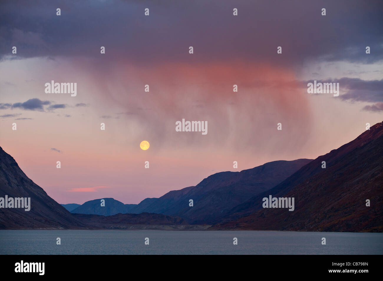 Storm clouds and full moon over Kangerlussuaq, also known as Söndre Strömfjord, one of the world's longest - Stock Image