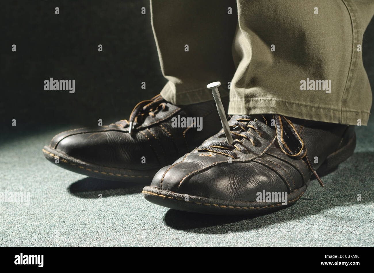 nail spike piercing shoe and foot holding man in place - Stock Image