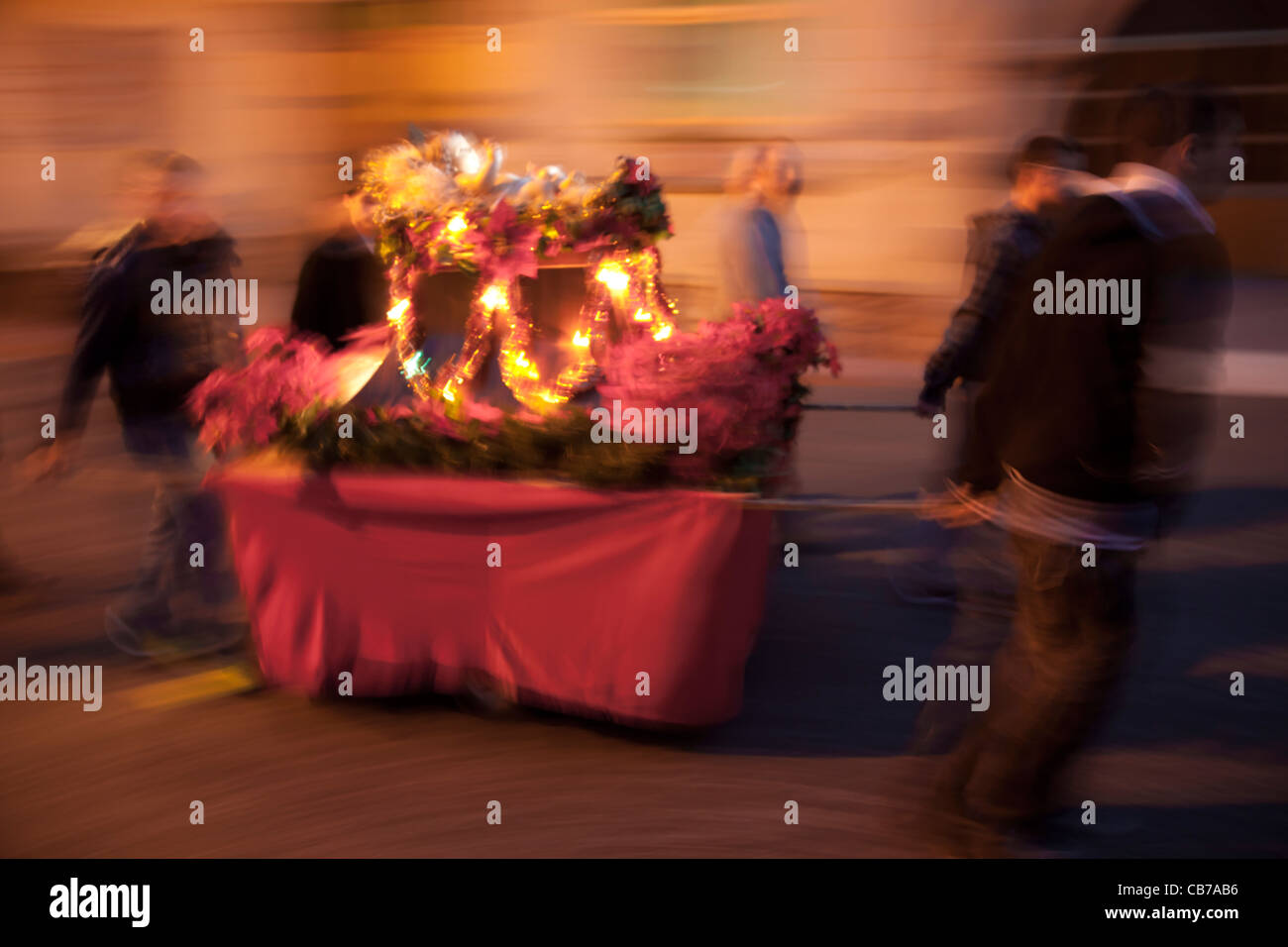 Youths walking around the town's streets with a cart that holds a statue of baby Jesus in Malta. - Stock Image