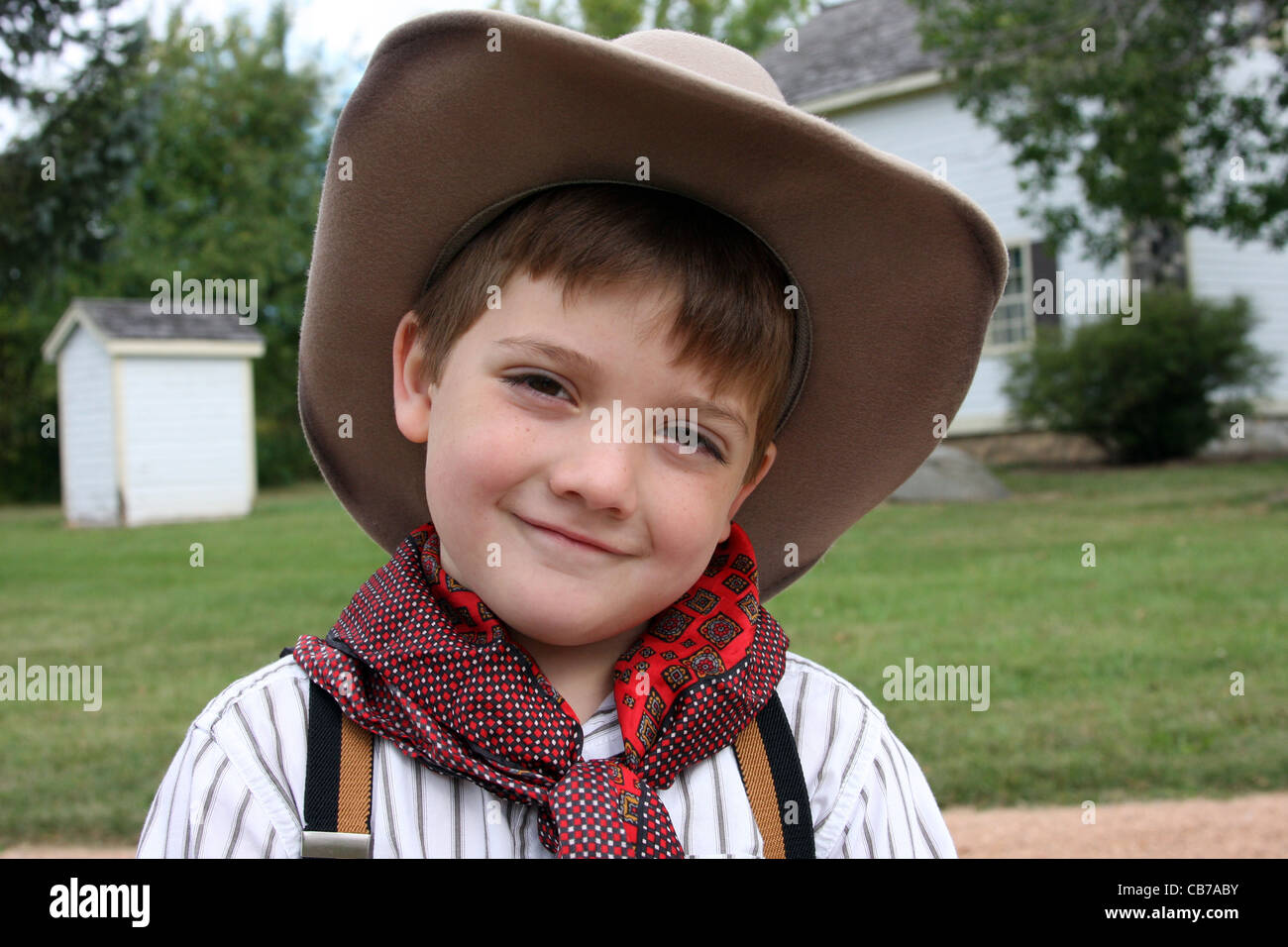 A young cowboy child tipping his hat Howdy in a greeting salute. C8HTAG  (RM). An adorable cowboy in front of a ranch house and outhouse - Stock  Image 75714337ae07