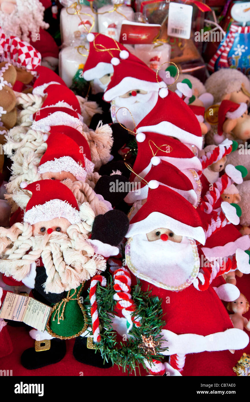 group of jolly hand crafted Santa Claus tree ornaments displayed for sale at Christmas market Mercado Medellin Roma - Stock Image