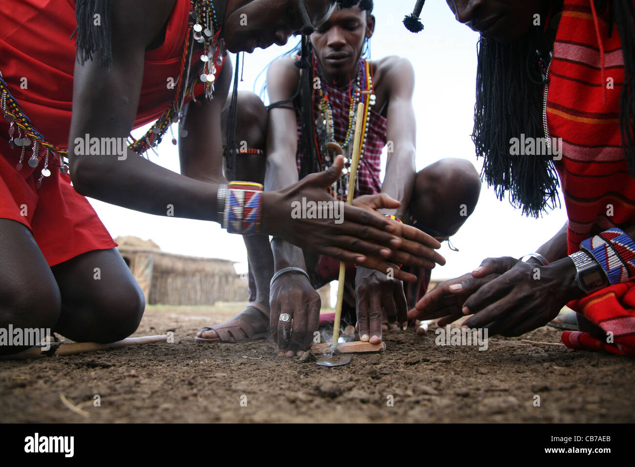 Young Masai men start a friction fire by rubbing two sticks together at their village in the Masai Mara National - Stock Image